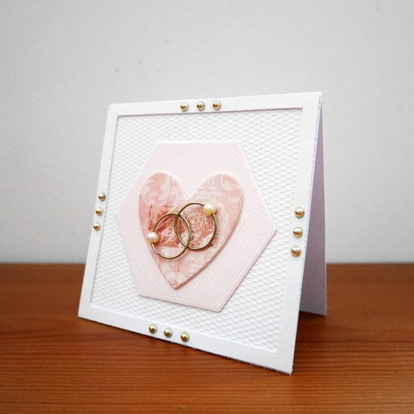 Vitt bröllopskort med vigselringar och gulddetaljer