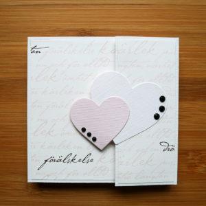 Vitt fotoalbum med mönstrat papper som har snirkliga ord i rosa och svart skrivet över sig. Ett rosa och ett vitt hjärta är placerat vid öppningen av albumet. Tre svarta dekorstenar är limmade på vardera hjärta.