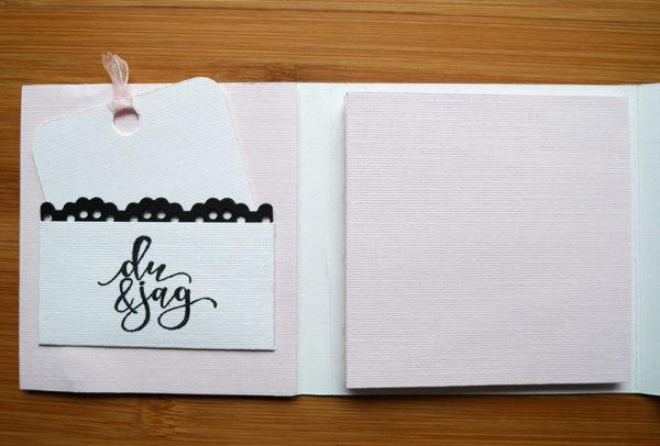 Vitt album med rosa flikar att placera bilder på. En vit ficka med svart spetskant och texten 'du & jag' med tillhörande vit etikett och rosa band.