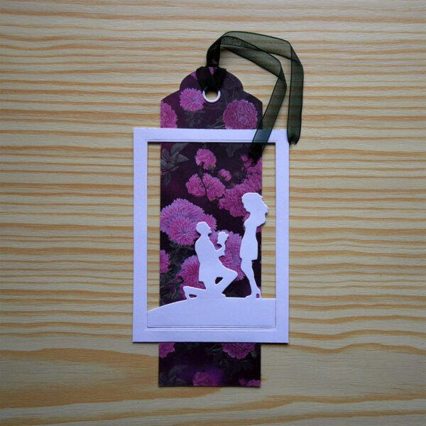 Etikett med rosa blommor och grönt band. Vit ram och silhuett som föreställer ett trolovat par.