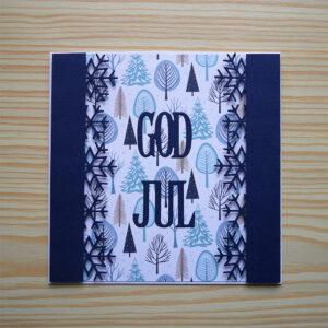 Kvadratiskt kort. Vit bas med ett mönstrat papper i vitt, blått och brunt som föreställer träd i olika stilar. Blå lodräta kanter med utskurna snöflingor inåt mitten. I samma blå färg står det 'god jul' i versaler på mitten av kortet.