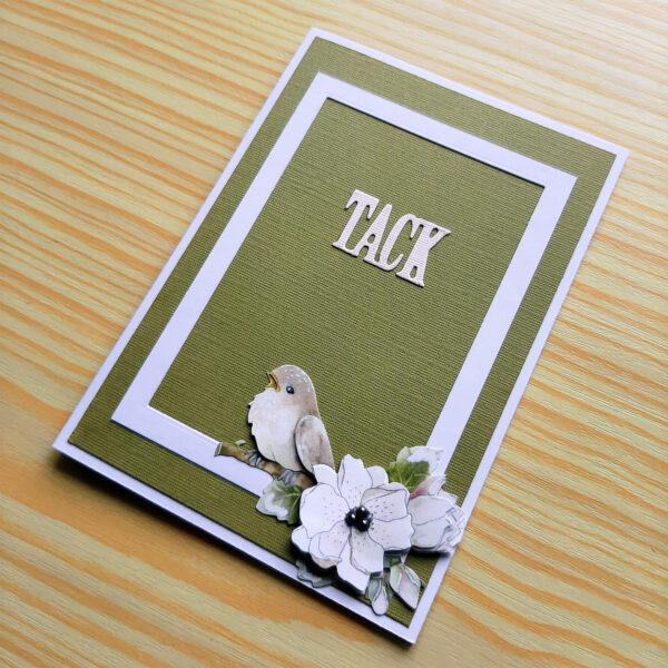 Grönt tackkort med vit ram, fågel och blomma.